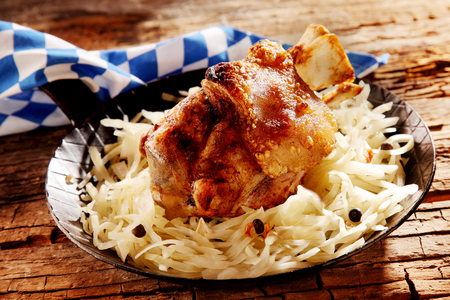 speciality: Crispy golden roasted pork knuckle served with cheese at a rustic Bavarian tavern offering speciality cuisine