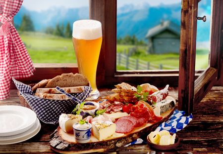 Bavarian tavern lunch with bread, assorted cold spicy sausage and meat, cheese and a long ice cold beer on a rustic wooden windowsill with a view of the Alps