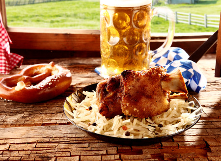 wiesn: Roasted pork knuckle or hock with a crispy golden rind served with a pretzel and cold beer at a tavern offering traditional Bavarian cuisine to tourists Stock Photo