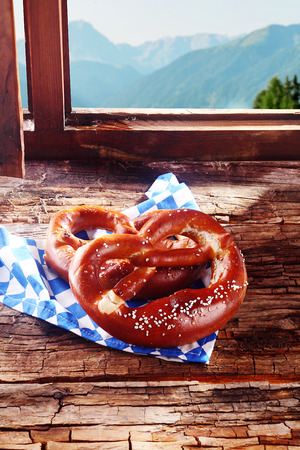 lunchtime: Traditional Bavarian pretzel, a brittle dried glazed and salted knotted biscuit, served in a tavern for a lunchtime snack o a window sill overlooking the alps outside