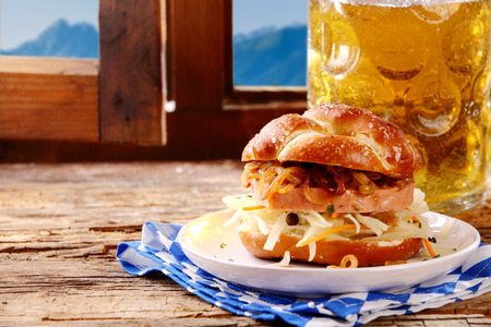 wiesn: Tasty regional Bavarian cuisine with a crusty roll filled with grated cheese and spicy beef and pork meat loaf served with a tankard of cold beer in a rustic alpine tavern