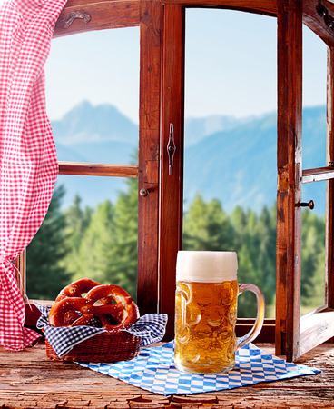wiesn: Cold beer and salty pretzels served for refreshments at a Bavarian tavern in front of a rustic wooden window overlooking the alps Stock Photo