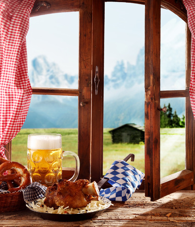 wooden window: Bavarian Roasted or grilled knuckle of ham served with a tankard of beer on a rustic wooden windowsill overlooking the Bavarian alpsRoasted or grilledigs trotter served with a tankard of beer on a rustic wooden windowsill overlooking the Bavarian alps