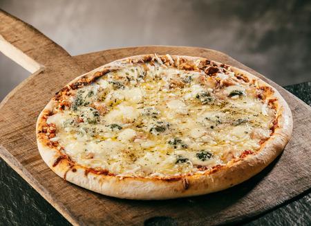 queso de cabra: Llama a la parrilla italiana Pizza de cuatro quesos se sirve muy caliente en una tabla de madera en una pizzería o restaurante para una merienda rápida sabrosa comida sabrosa o para llevar, opinión de alto ángulo Foto de archivo