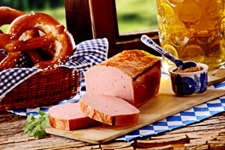 MEAT LOAF: Tasty Bavarian tavern lunch with speciality beef and pork meat loaf served with a pretzel and cold beer on a rustic wooden window sill Stock Photo