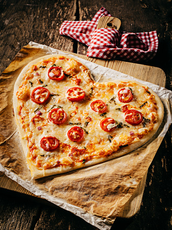 rustic kitchen: Baked heart-shaped homemade pizza topped with mozzarella and tomato slices, on parchment paper on a cutting board near a checkered red and white kitchen towel, on a rustic table, high-angle close-up Stock Photo