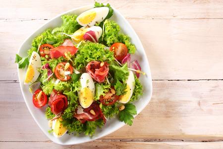 ensalada de verduras: Opinión de alto ángulo de una ensalada de verduras hervidas nutritiva con rebanadas de huevo, servido en un plato blanco encima de una mesa de madera Foto de archivo