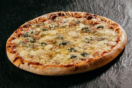 불꽃 구이 이탈리아어 네 치즈 피자, 녹은 모짜렐라, 고르곤 졸라, 염소 우유와 허브 양념 에멘탈 치즈의 혼합물을 얹어 낮은 각도보기를 닫습니다