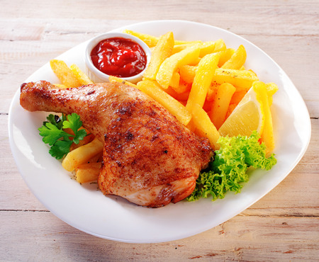 Close up Gourmet Appetizing Chicken and Fries Meal on a White Plate with Fresh Lettuce, Lemon Slice and Ketchup Sauce.