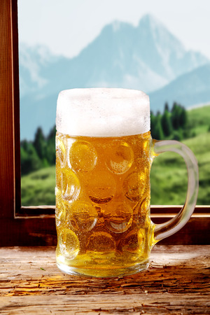 tankard: Tankard of cold beer with a large frothy head served on a rustic wooden windowsill in a Bavarian tavern with a view of the alps, conceptual of the Oktoberfest