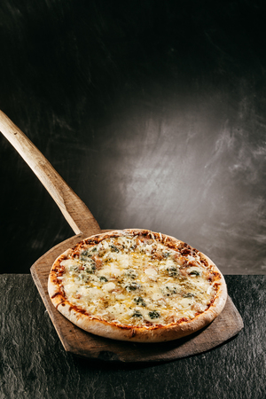 Four Cheese Italian Pizza on a restaurant menu with a flame grilled steaming hot pizza served on a wooden board in front of a blank chalkboard with copyspace for a menu or recipe Stock Photo