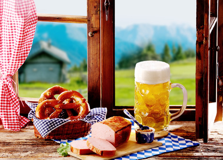 tankard: Tasty Bavarian meat loaf served with pretzels and a large glass tankard of cold lager or beer for a traditional tavern lunch during the Oktoberfest Stock Photo