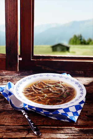 wiesn: Speciality liver spaetzle in broth served in a Bavarian restaurant offering regional cuisine during the Oktoberfest on a windowsill overlooking the alps