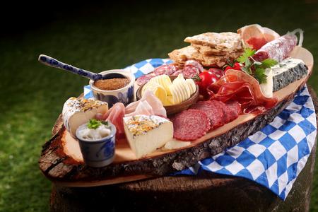 jamon y queso: Carne de Baviera Gourmet y tabla de quesos con salchichas picantes variados, jamón y salami con una variedad de quesos, salsa y mantequilla sirven al aire libre en un tocón de árbol rústico en la luz del sol