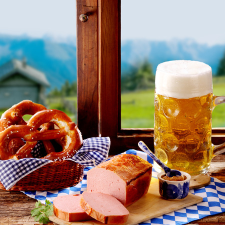 wiesn: Traditional Bavarian cuisine for Oktoberfest with regional pork and beef loaf served with salted pretzels, a spicy dip and large glass tankard of cold beer in front of a window with a view of the alps