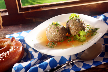 lunchtime: Savory liver dumplings with fresh parsley and a sauce served as a lunchtime snack with pretzels in a traditional Bavarian tavern Stock Photo