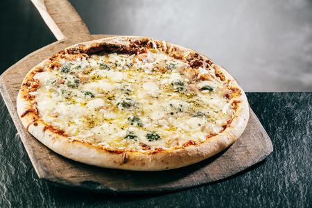 queso de cabra: Cocer al vapor caliente llama a la parrilla cuatro quesos pizza italiana sirvió en una tabla de madera de mango largo en una pizzería o restaurante, vista de cerca Foto de archivo
