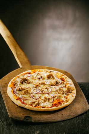 restaurante italiano: Recién salido del horno bien caliente pizza italiana que se sirve en un restaurante o pizzería en una tabla de madera de mango largo con copyspace Foto de archivo