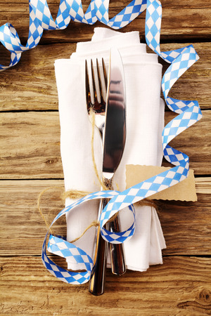 table decoration: Decorative Oktoberfest table setting in a tavern or restaurant with a knife and fork tied with a tag on a napkin with a coiled party streamer in the blue and white Bavarian colors, overhead view Stock Photo