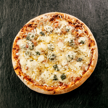 Speciality Italian food - Four Cheeses Pizza topped with mozzarella, emmental, gorgonzola and goat milk cheese flavored with herbs, overhead view on a dark background Stock Photo