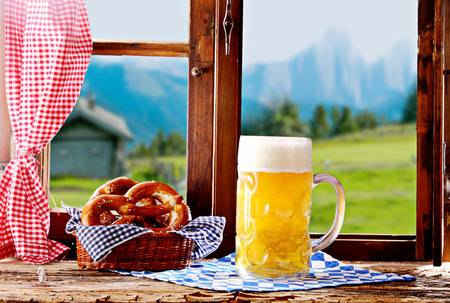 Tankard of cold draft beer with a frothy head and basket of savory salted pretzels standing on a windowsill in a rustic restaurant or tavern overlooking the Bavarian alps, conceptual of Oktoberfest Stock Photo