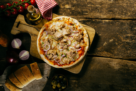 Tasty seafood tuna pizza in a rustic kitchen served with freshly baked sliced baguette and condiments, viewed from overhead on an old wooden table with copyspace