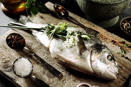 seasoning: Close Up of Fresh Whole Raw Fish on Rustic Wooden Cutting Board Surrounded by Fresh Herbs and Spices for Seasoning Stock Photo