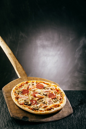 long handled: Flame grilled ham and pepperoni pizza with mushrooms and melted mozzarella being served piping hot on a long handled wooden board in a pizzeria with copyspace over steam
