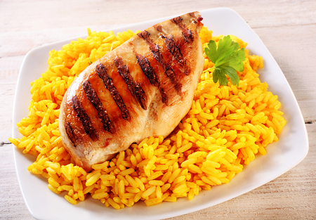 Overhead of Grilled Skinless Chicken Breast on Bed of Seasoned Yellow Rice and Garnished with Fresh Herb, on Oblong White Plate on Rustic White Wooden Table