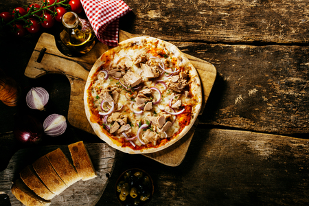 rustic food: Preparing delicious homemade tuna pizza in a rustic kitchen on an old wooden counter served with fresh bread and condiments, overhead view with copyspace