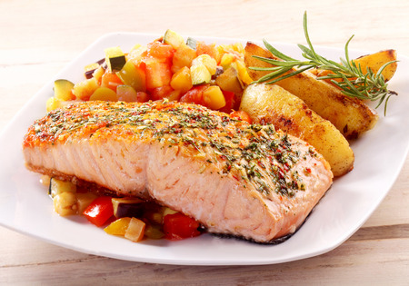 grilled fish: Herb Roasted Fillet of Salmon Served on White Plate with Roasted Potato Wedges and Fresh Chopped Salsa Garnished with Herbs