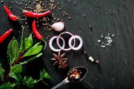 onion: Vista elevada de varias hierbas y especias frescas, rodajas de cebolla y pimientos picantes dispersos en gris oscuro superficie de la piedra con el espacio de la copia