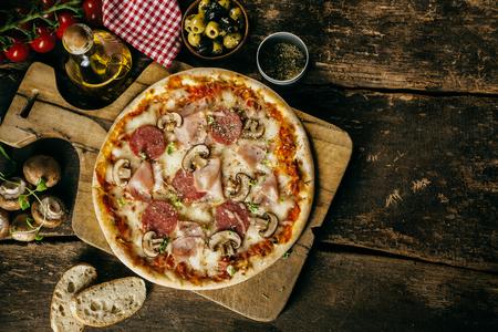 pizza: Jamón caseras, embutidos y setas de pizza servida en una tabla en una vieja mesa de la cocina de madera rústica rodeada de los ingredientes frescos de la receta, vista aérea con copyspace
