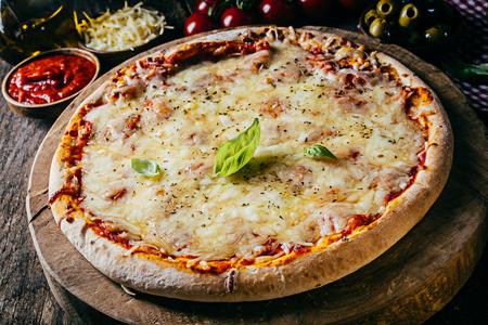restaurante italiano: Fresco al horno de pizza margarita italiana con queso mozzarella derretido en una corteza crujiente con guarnición de albahaca en una cocina rústica