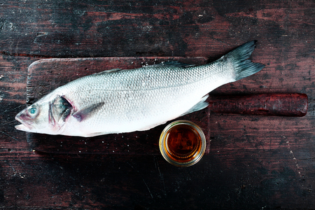 high angle: High Angle View of Fresh Raw Whole Fish on Rustic Wooden Cutting Board with Small Dish of Oil Stock Photo