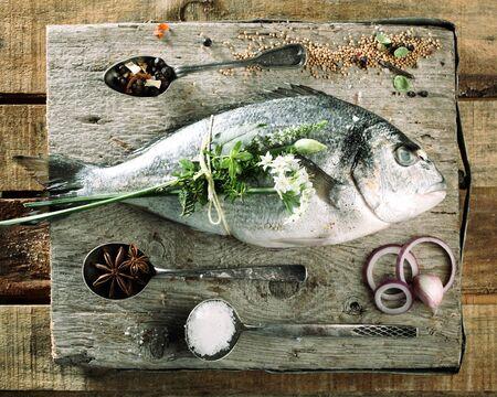 yerbas: Opinión de alto ángulo fresco pescado crudo en rústica tabla de cortar de madera, rodeado de varias especias frescas y hierbas para sazonar Foto de archivo