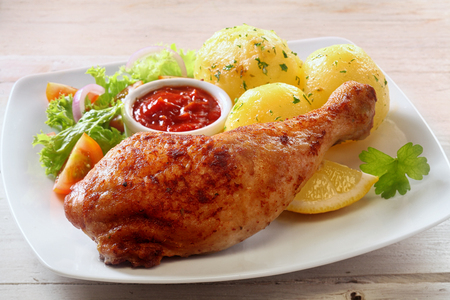 roasted chicken: Close Up of Healthy Chicken Dinner - Roasted Chicken Leg on White Plate with Fresh Green Salad and Roasted Potatoes Served on Rustic White Wooden Table Surface Stock Photo