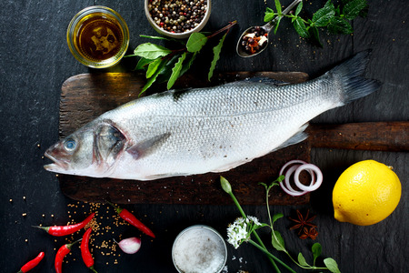 素朴な木製のまな板に囲まれて新鮮なハーブやスパイス調味料と飾りのための新鮮な生全体の魚のハイアングル