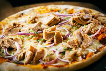 atun: Pizza de atún sabroso con hierbas y cebollas en una mozzarella derretido y tomate topping para un sabroso bocado de comida rápida, servido todo en una vista de primer plano