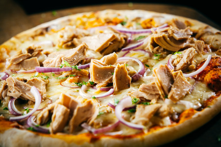 pizzas: Savory tuna pizza with herbs and onions on a melted mozzarella and tomato topping for a tasty fast food snack, served whole in a close up view Stock Photo