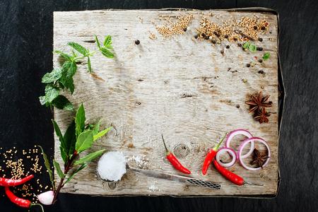 tablero: Vista elevada de la Junta de corte rústica con diversas frescas hierbas, especias y pimientos dispersas en su superficie con Espacio en blanco Foto de archivo