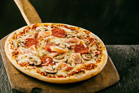 Freshly baked Italian pizza with ham, mushrooms and salami served whole on a wooden board on a rustic wooden counter in a pizzeria or restaurant