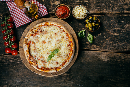Home baked margarita pizza with fresh ingredients including tomatoes, mozzarella cheese, olives , basil and oil on a rustic wooden kitchen counter, viewed from above