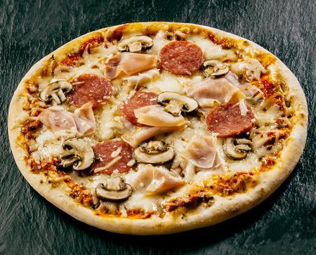 hongo: Para llevar la llama a la parrilla pizza italiana con salami, jamón y setas en mozzarella derretida sirvió sin cortar sobre una mesa rústica oscura, opinión de alto ángulo