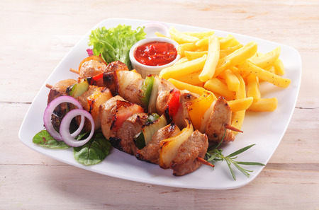fry: High Angle View of Healthy Kebab Dinner - Skewers of Meat and Vegetables Served with French Fries and Ketchup Dipping Sauce Served on White Plate