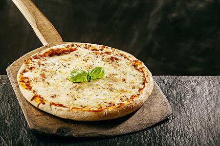 restaurante italiano: Llama a la parrilla sabrosa pizza margarita italiana servida en una pizzería en una tabla de madera de mango largo sobre una mesa rústica, copyspace detrás