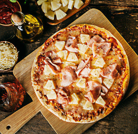 Freshly baked crusty ham and pineapple Hawaiian pizza on a wooden board surrounded by ingredients in individual dishes on a rustic wood kitchen counter, overhead view Stok Fotoğraf