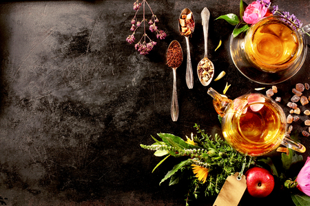 Overhead view of various sorts of tea. Flavoured with Assorted Herbs, an apple, rose with a teapot and a teacup on a rustic black metal board Stockfoto