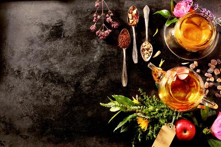 Bovenaanzicht van verschillende soorten thee. Gearomatiseerd met Kruidenassortimenten, een appel, roos met een theepot en een theekopje op een rustieke black metal raad