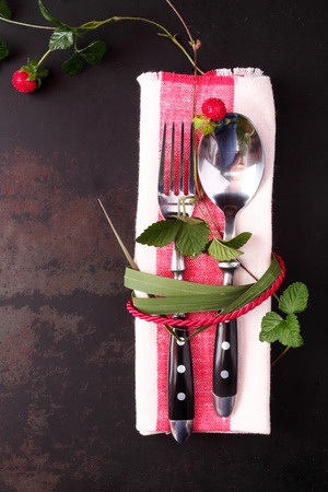 tied down: Stylish table setting with red cord and trailing leaves with a wild strawberry tied around a spoon and fork on a red and white napkin, close up overhead view